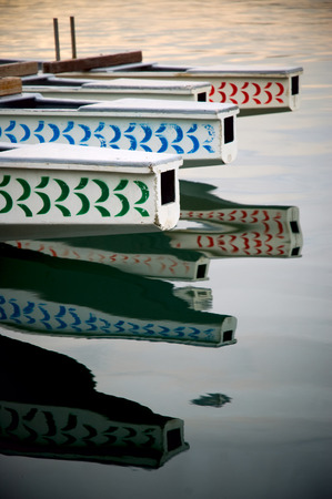 The helm of four dragon boats reflecting on the ocean surface