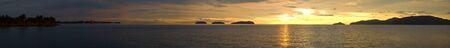 A ultra wide panorama view of a golden sunset ocean