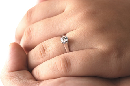 A man holding his fiances hand with an engagement ring on