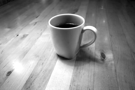 A black and white photograph of a cup of cafe latte on wooden table