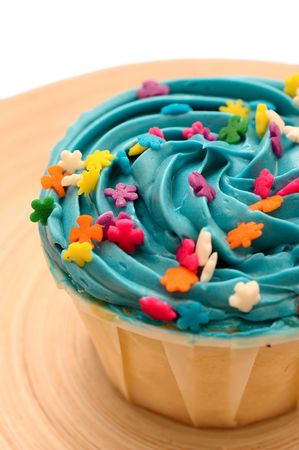 A blue candy cup cake with colorful star toppings on a plate