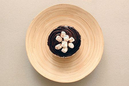 A chocolate cup cake with marshmallow toppings