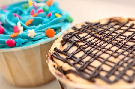 Two extremely delicious cup cakes, chocolate mocha and blue candy