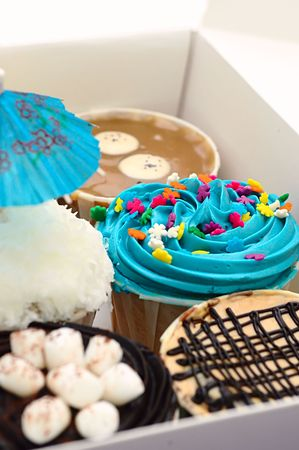 A box full of fancy and colorful cup cakes for sale