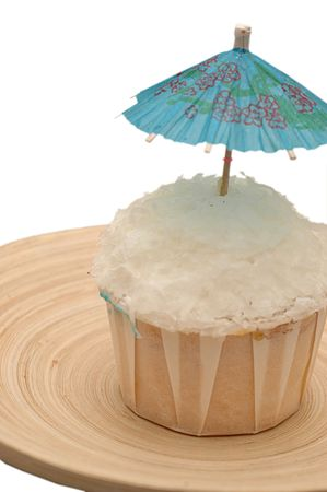 A white topping cup cake decorated with a blue umbrella Stock Photo