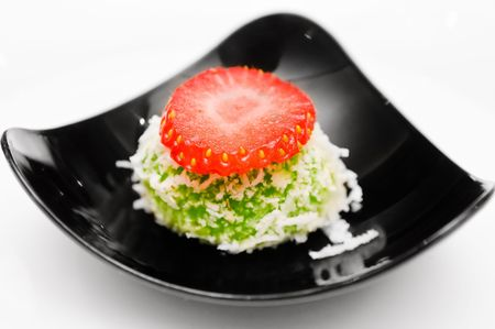 Green dessert with coconut and strawberry topping. White background