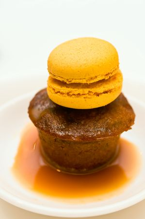 Sticky pudding dessert in a plate with caramel sauce with marzipan decoration