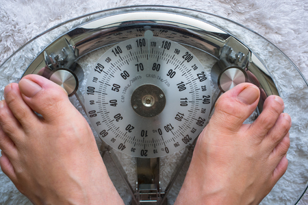 Photo showing two feet on a modern analog scale taking weight Stock Photo