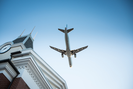 Plane flying by over a building with a clock Stock Photo