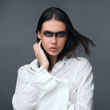 Portrait of a beautiful girl in a white shirt with bright makeup.Studio shooting