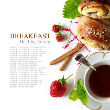 Delicious breakfast of tea, fresh bread rolls with sesame seeds and strawberries  isolated  photo