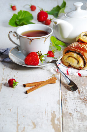 Delicious breakfast of tea, fresh bread rolls with sesame seeds and strawberries  photo