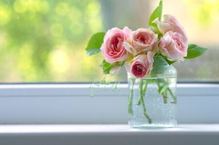 cosiness: Bouquet of flowers pink roses on the window. Rustic still life. Cosiness in the house.