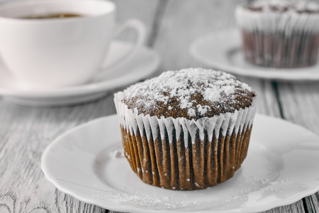 Homemade chocolate muffins with powdered sugar and coffee on a wooden background. Stock Photo