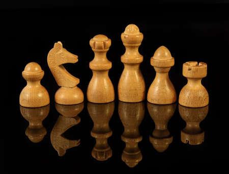 Wooden chess pieces on black background