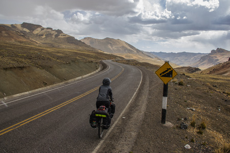 Touring cyclist fully loaded going downhill in the peruvian moutains