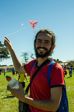 prodigious: Smilling middle age man playing with a strange red kite