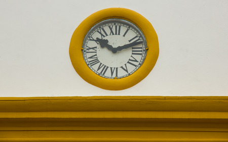 vespers: Old Roman Clock in a Church Wall with yellow details Stock Photo