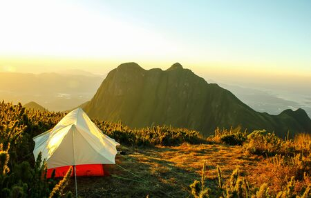 Tent on the top of a mountain with a nice view of another mountain