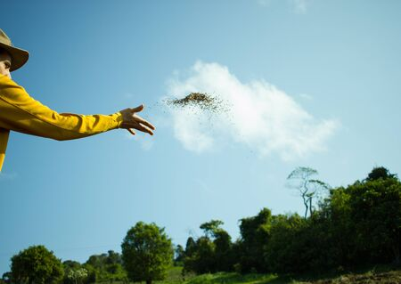 Farmer Spreading Oat Seeds on the Land