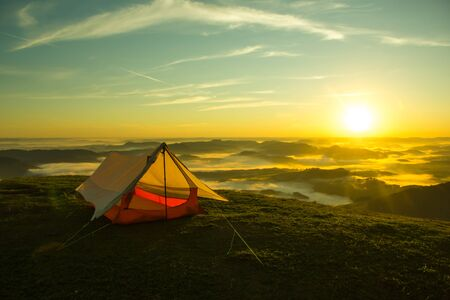 Simple Tent on the Top of a green mountain with the Sunrise