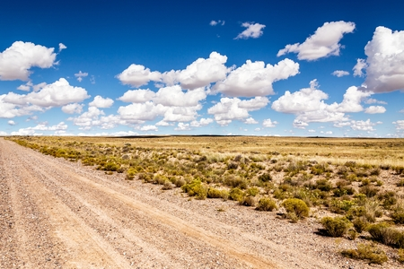wasteland, dirt road in the desert with clouds, desert Stock Photo