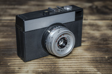 An old Russian manual film camera mounted on a wooden table Stock Photo