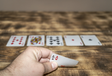 A hand holding two shots, a winning combination in playing cards