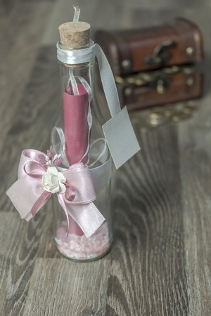A bottle of pink paper, greasy and blossom behind chest with treasure Stock Photo