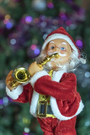 Santa Claus plays a trumpet for a new year and a Christmas In the background is seen by bright colors of different lights Stock Photo