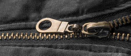 Macro close up of a golden zipper on a black jacket Standard-Bild