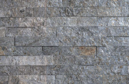 The texture of the natural stone cut in the shape of the tiles on the wall
