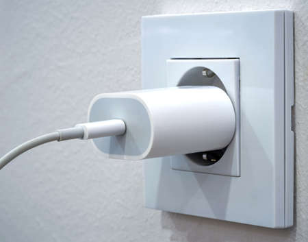 Close up of a mobile phone charger plugged into an outlet