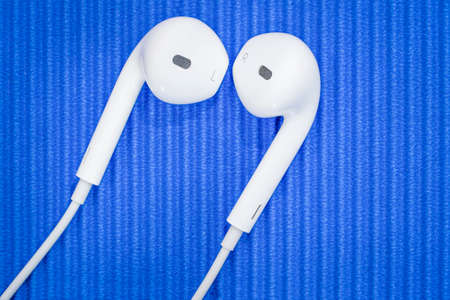 Macro close up of a white mobile phone headset on a blue background