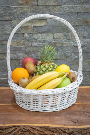 Fruit arranged in a basket on a wooden table next to a stone wall