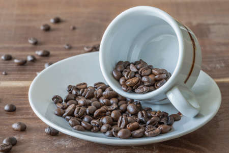 An inverted cup of coffee with coffee beans around Standard-Bild