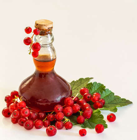 Currants next to a bottle of currant brandy on a leaf Standard-Bild