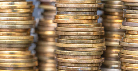 Macro close up coins arranged in height on a blurred background Standard-Bild