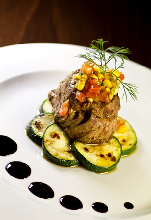 plating: Beef tenderloin steak with tomato corn salsa on a bed of grilled zucchini. Stock Photo