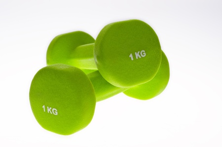 Pair of green dumbbells on white background. Stock Photo