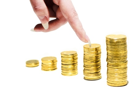 Stack of coins and hand on a white background with shallow depth of field Stock Photo