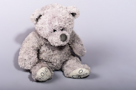 Teddy bear waiting for a friend on a gray background