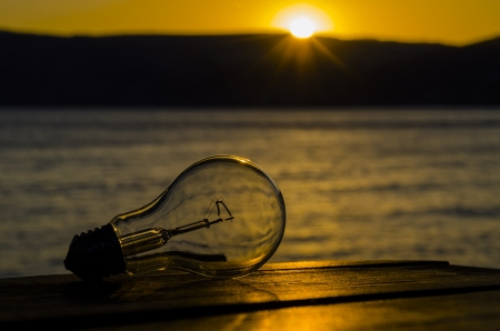 Bulb, lying on a wooden table, on background the bright sun, the mountains and the sea