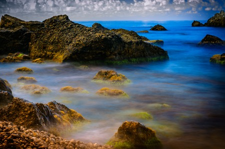 Overgrown with algae and mud stones washed by sea water  A slow shutter speed  Stock Photo