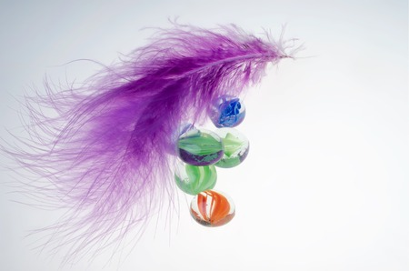 Purple feather and decorative stones on a white background.
