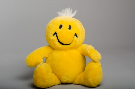 Yellow smiley, positive stuffed toy for children on a gray background. Stock Photo