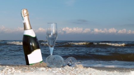 A bottle of champagne and two glasses on a background of a sea wave. Romantic composition.