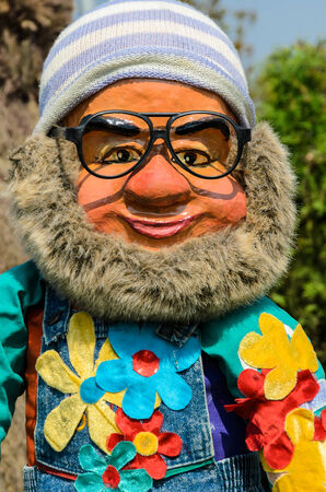 It is A ceramic statue of a leprechaun with soft beard, wearing a knit hat and glasses