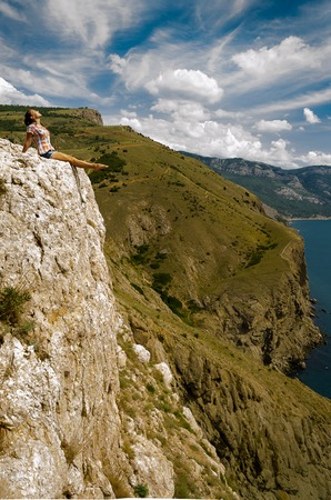 Young woman  on a rock. Freedom and fearlessness.. Summery. Tourism and hiking.