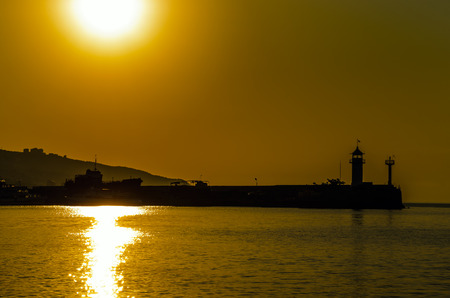Silhouette of a lighthouse in the warm rays of dawn. Yellow. Stock Photo